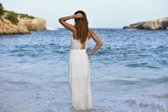 Free Woman Looking Thoughtful At Sea Water In Summer Holiday Enjoying Vacation Relaxed Wearing White Beach Dress Stock Images - 56499204