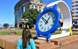 Woman looking at the time in a giant clock. Public park close to Riazor Beach. La Coruna, Spain, 22 Sep 2018. La Coruna, Galicia, Rias Altas, Spain. Giant clock royalty free stock photos