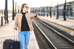Woman looking at the time and watch while waiting for train. royalty free stock photos