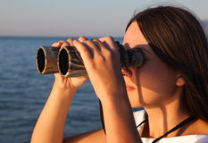 A woman is looking to the binocular Stock Photo