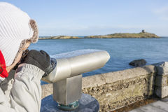 Woman looking to Dalkey island by binoculars Royalty Free Stock Images