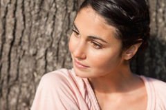 Woman looking to her side while sitting by a tree  Stock Images