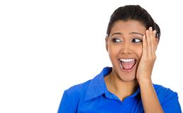 Woman looking to left shocked and surprised. Closeup portrait of a happy young pretty woman looking to left shocked and surprised in full disbelief hand on cheek Royalty Free Stock Photography