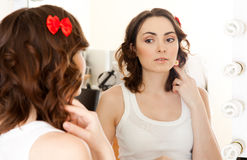 Woman looking to the mirror Royalty Free Stock Images
