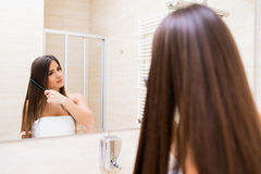 Woman looking to mirror at home bathroom. Young woman looking to mirror at home bathroom stock photo