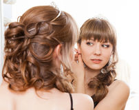 Woman looking to the mirror and putting earrings Royalty Free Stock Photography