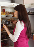 Woman looking in to pan from  fridge Stock Images