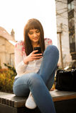 Woman looking to phone in street Stock Photography