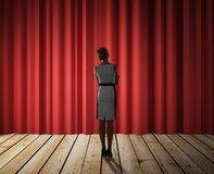 Woman looking to red curtain Royalty Free Stock Image