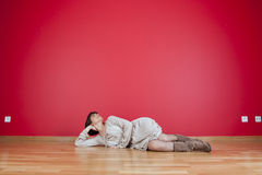 Woman looking to a red wall Stock Photography