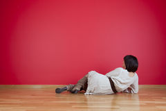 Woman looking to a red wall Stock Images