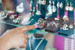 Woman looking to showcase or shop window. Shopping woman chooses jewelry in store Stock Photo