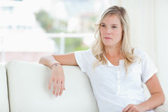 A woman looking to the side as she sits on the couch Stock Image