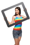 Woman looking to the side through tablet frame Royalty Free Stock Images