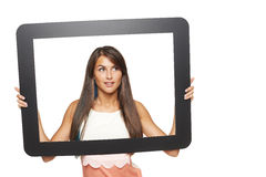Woman looking to side through tablet frame. Smiling young woman looking to side through tablet frame, over white background Royalty Free Stock Image