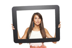 Woman looking to side through tablet frame Royalty Free Stock Image