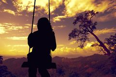 A woman looking to sunset scene and sitting on royalty free stock photography