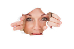 Woman looking through torn paper Royalty Free Stock Photography