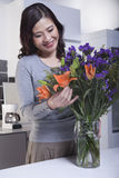 Woman Looking and Touching a Bouquet of Flowers in the Kitchen Stock Photos