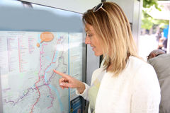Woman looking on transport map in the city Royalty Free Stock Photo