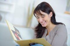 Woman looking at travel diary memories. Woman looking at a travel diary memories Royalty Free Stock Photo