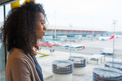 Black woman looking trough airport window Royalty Free Stock Images