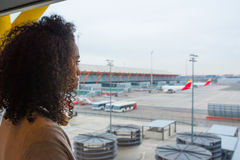 Black woman looking trough airport window royalty free stock photography