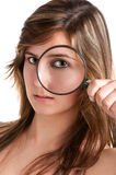 Woman looking trough a loupe. Woman looking trough a magnifying glass, isolated in a white background Royalty Free Stock Photography