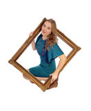 Woman looking trough picture frame. Royalty Free Stock Photos