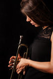 Woman looking on a trumpet Stock Image