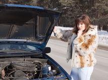 Woman looking under  car hood Stock Photo