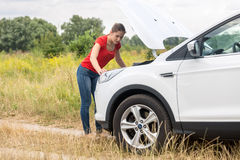 Woman looking under the hood of overheated car at meadow Royalty Free Stock Photos