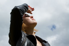 Woman looking up. A pretty young woman in a black leather jacket and wearing glasses looks up into the sky with an arm raised shielding the light Stock Photo