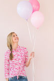 Woman Looking Up At Balloons Against Pink Background