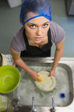 Woman looking up from doing the washing up Royalty Free Stock Photos
