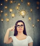 Woman looking up at dollar idea light bulbs above head deciding how to earn morney. Portrait of a thinking young woman looking up at dollar idea light bulbs royalty free stock photography