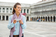 Woman looking up from her device while on St. Marks Square Stock Photo