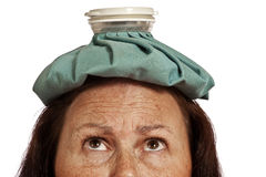 Woman Looking Up At Ice Pack. Horizontal shot of a woman looking up at an ice pack for stress headache.  On white background Royalty Free Stock Photos