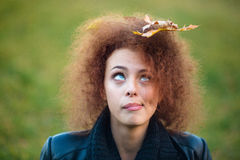 Woman looking up on leave in her curly hair Stock Images