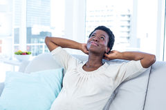 Woman looking up while relaxing on sofa at home. High angle view of woman looking up while relaxing on sofa at home Stock Photos