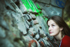 Woman looking up stone wall. Young brunette woman in the bottom right corner of the photo looking upward while leaning on an uneven stone wall covered with royalty free stock images