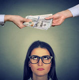 Woman looking up at two hands exchanging money. Woman in glasses looking up at two hands exchanging money Royalty Free Stock Images