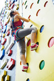 Woman is looking upwards on the rock-climbing wall Stock Photography
