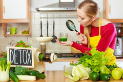 Woman looking at vegetable juice through magnifying glass. Drinks good for health, diet breakfast concept. Young woman in kitchen holding green healthy vegetable stock photo