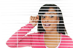 Woman looking through venetian blinds Royalty Free Stock Photography