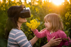 Woman looking through VR device and playing with her daughter Stock Images