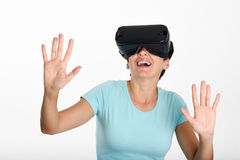 Woman looking in VR glasses and gesturing with his hands. Royalty Free Stock Photos