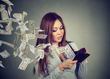 Woman looking at wallet money dollar banknotes flying out away stock image