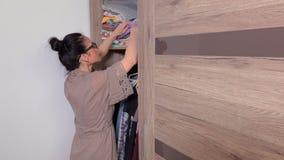 Woman looking in wardrobe and close door stock video footage