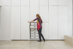 Woman Looking In Wardrobe In Empty Apartment. Full length rear view of a young woman looking in wardrobe in empty apartment Stock Images
